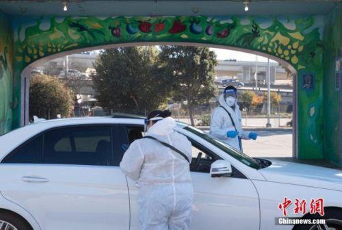 """当地时间12月1日,设立在美国加州旧金山Alemany农贸市场的""""得来速""""式新冠病毒检测站向市民提供检测服务。中新社记者 刘关关 摄"""