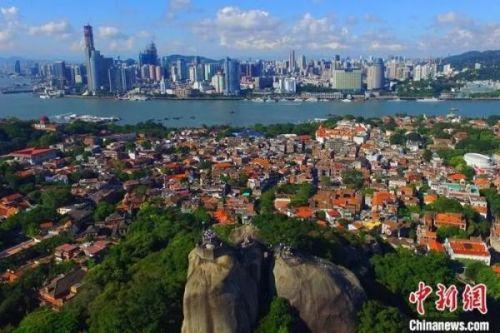 资料图:鼓浪屿上的红砖古厝与对面的现代化建筑遥相辉映。中新社记者 王东明 摄
